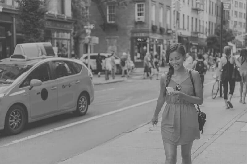 Young woman walking on busy city street